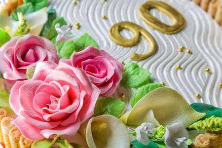 Delicious cake with roses, lily, leaves and figures 90 Years on light blue wooden table close up with selective focus. Stock Photo