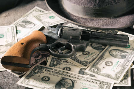 Crime concept. Black gun with dollar banknotes and hat. Toned image. Stock Photo
