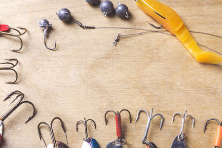 jigging: Different fishing tackles and plastic worm on wooden board background. Stock Photo