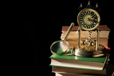 Literature concept. Magnifying glass near vintage clock on old books against black background. Stock Photo