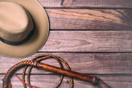旅行や冒険のコンセプトです。ビンテージの fedora 帽子と木製のテーブルに鞭。平面図です。
