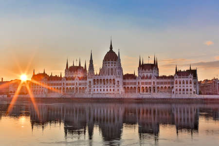 Parliament and riverside in Budapest Hungary during sunrise with sunbeams.