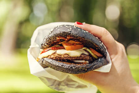 Woman hand holding tasty burger with black bread outdoors. Stock Photo