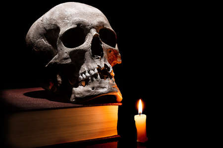 Human skull on old book with burning candle on black background.