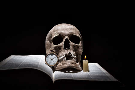 Human skull on old open book with burning candle and vintage clock on black background under beam of light. Archivio Fotografico