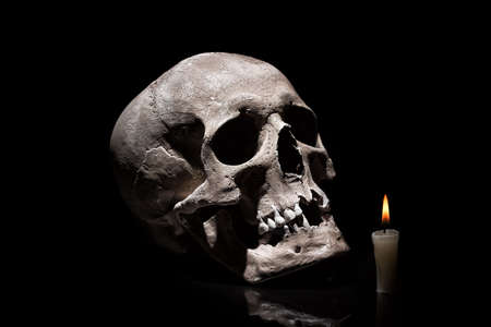 Human skull with burning candle on black background with reflection close up.