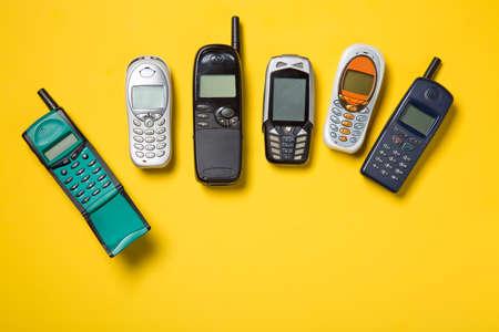 Oude mobiele telefoons op gele achtergrond