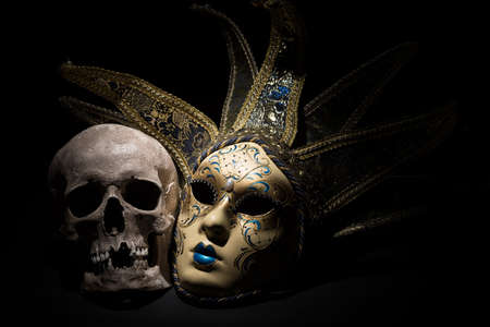 Human skull with venetian mask on a black background. Theater and drama concept. Stock Photo