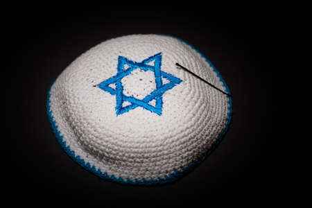 Knitted kippah with blue David star on black background close up. Seder concept. Stock Photo