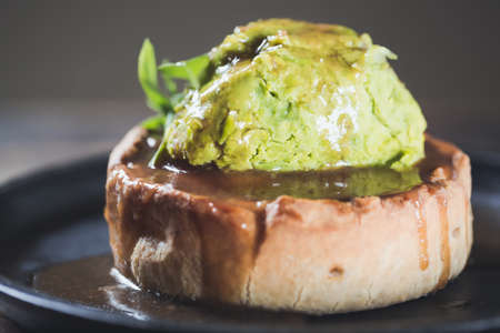 Game pie with duck meat in serving dish with peas puree and spinach leaves close up.