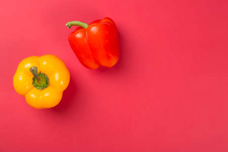 Draufsicht des hellen gelben und roten Paprikapaprikas auf rotem Hintergrund Standard-Bild - 83129659