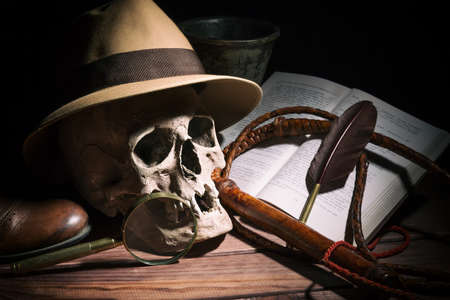 Adventure and archeology concept. Skull with fedora hat, bullwhip, book, quill, shoe, mortyr and magnifying glass on wooden table and black background. Still life Stock Photo