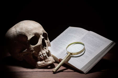 Human skull near old open book and magnifying glass on black background