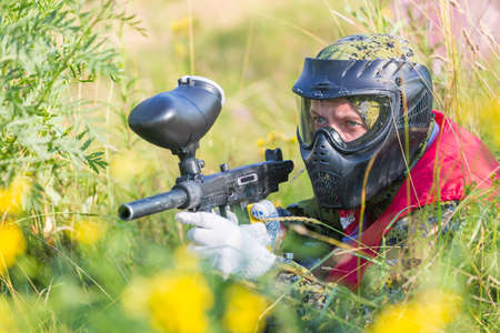 gunfire: Paintball sport player in protective uniform and mask playing with gun outdoors and sneaking in grass Stock Photo
