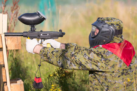 gunfire: Paintball sport player in protective uniform and mask playing and shooting with gun outdoors