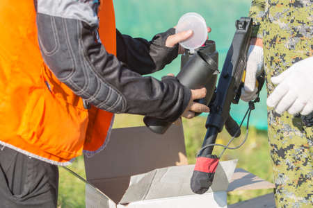gunfire: Two persons loading paintball gun with balls outdoors Stock Photo