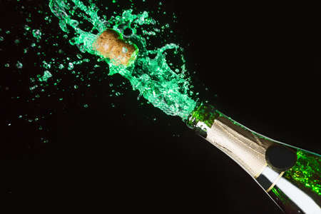 popping cork: Celebration alcohol theme with explosion of splashing green absinth on black background
