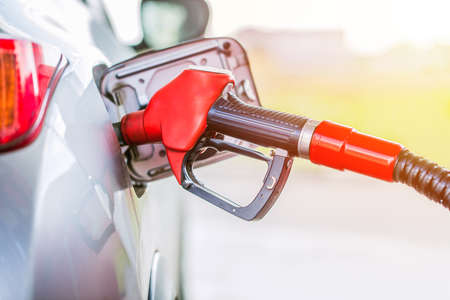 expensive: Petrol pumping gasoline at gas station. Close up and toned Stock Photo