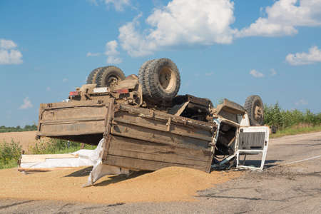 Accident on the road. Overturned truck with sand lies on the ground after a crash. Stock Photo