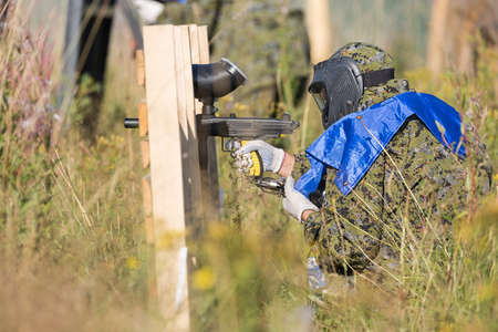 Paintball sport player in protective uniform and mask playing and shooting with gun outdoors.