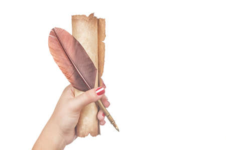 Literature concept. Female woman hand holds a feather quill pen with old vintage scroll isolated on white background Stock Photo