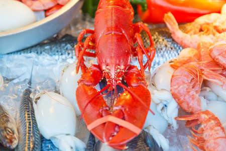 foodies: Fresh seafood red crawfish, shrimps, fish, calamary meat on ice at traditional seafood restaurant in Venice, Italy. Outdoor terrace Stock Photo