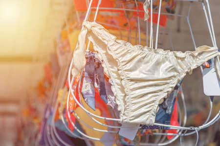 Swimming suits hanging for sale on the market. Toned.
