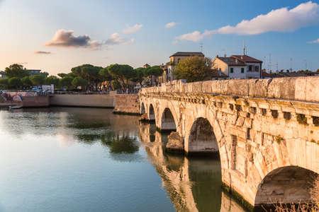 Historical roman Tiberius bridge over Marecchia river during sunset in Rimini, Italy.