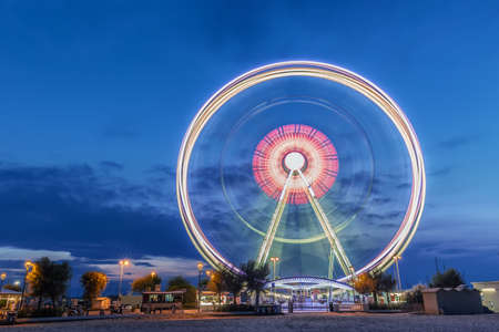 Spinning ferris wheel at sunrise blue hour in Rimini, Italy. Long exposure abstract image.