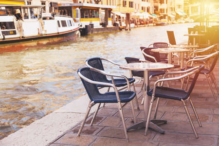 dining table and chairs: Restaurant tables and chairs with vaporetto ships in the background in Venice, Italy. European travel, outdoor dining and cuisine