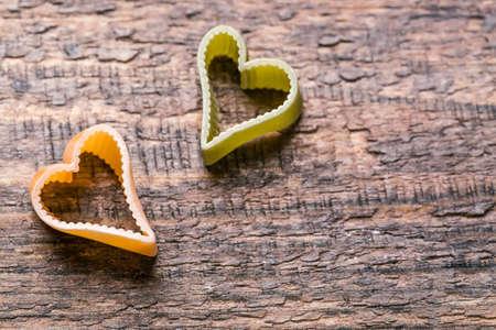 Two heart shaped italian pasta on wooden background. 版權商用圖片