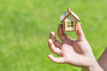Female hand holding small wooden house. Household concept Stock Photo
