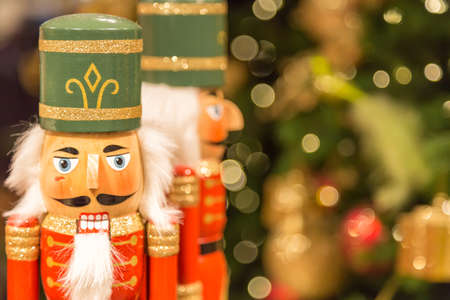 Soldier nutcracker statues standing in front of decorated Christmas tree with bokeh lights.