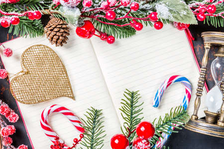 Christmas fir tree branches, decorations, angel, candy canes, frozen red berries, cone and vintage hourglass frame on notebook, copy space for text. Can be used for Christmas or new year project.