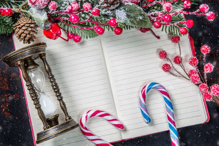 Christmas fir tree branches, decorations, candy canes, frozen red berries, cone and vintage hourglass frame on notebook with snow, copy space for text. Can be used for Christmas or new year project. Imagens
