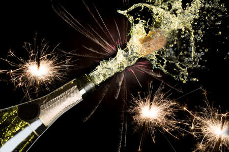 Celebration and holiday theme. Bright festive Christmas sparklers with fireworks and splashing champagne with popping cork on black background. Stock Photo
