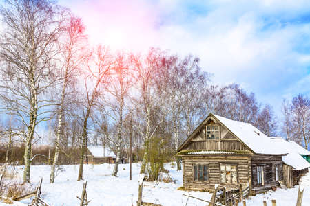 Winter landscape with old wooden house and trees with sunlight and blue cloudy sky. Amazing winter scene.