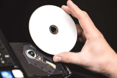 Male hand inserting a DVD into a disk drive