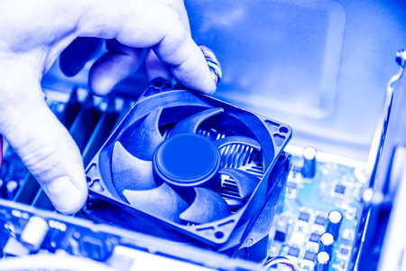Technician hands installing CPU cooler fan on a computer pc motherboard. Toned image. Foto de archivo