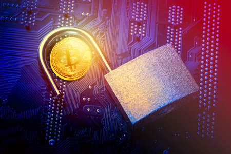 Bitcoin with opened padlock on computer motherboard. Crypto currency Internet data privacy information security concept Stock Photo