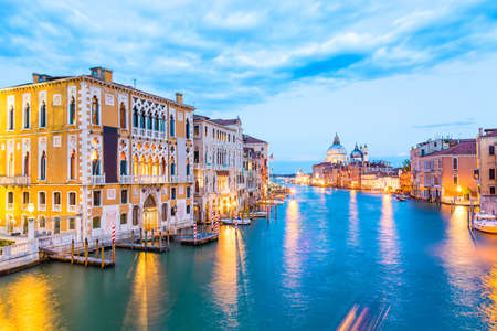 Basilica Santa Maria della Salute, Punta della Dogona and Grand Canal at blue hour sunset in Venice, Italy with boats and reflections