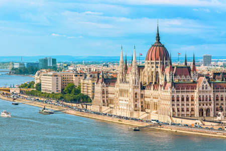 Travel and european tourism concept. Parliament and riverside in Budapest Hungary with sightseeing ships during summer day with blue sky and clouds.