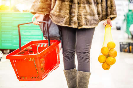 Woman holding red shopping basket and oranges in the supermarket store. Shopping concept