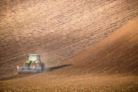 Beautiful autumn landscape with working tractor in south Moravia, Czech Republic. Agriculture concept. Czech TUscany. Moravian waving fields.