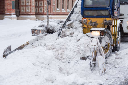 Tractor cleaning the streets of large amounts of snow in city after snowstorm. Winter time concept