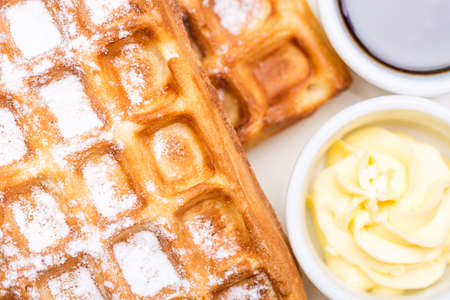 Whole wheat Belgium waffles on plate with butter and maple sauce. Selective focus.