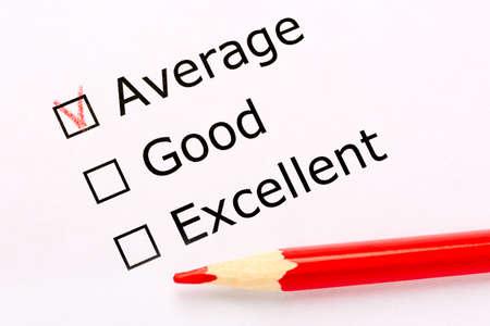 Feuille de papier blanc avec cases à cocher et crayon rouge. L'enquête demande à l'opinion des personnes si elle est moyenne, bonne ou excellente. Satisfaction du client.
