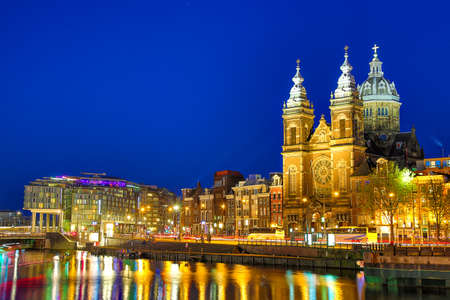 Canal and St Nicholas Church in Amsterdam at twilight, Netherlands. Famous Amsterdam landmark near Central Station