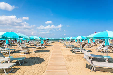 Beach chairs and umbrellas in Rimini, Italy during summer day with blue sky. Summer vacation and relax concept