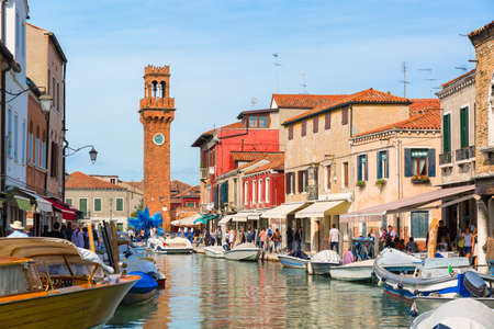 Murano island in the summer season. Canal and Murano campanile during sunny day. Famous tourist place in venice, Italy. 스톡 콘텐츠
